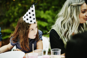 Young girl wearing party hat leaning on table